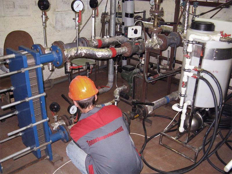 На фото показан процесс обслуживания элеваторной системы отопления.