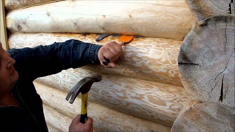 Процесс конопатки сруба